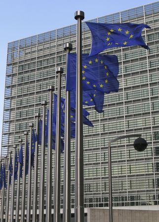 european community: European flags waving in the wind, before the European Commission Berlaymont building in Brussels, Belgium Stock Photo
