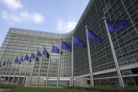 benelux: European flags waving in the wind, before the European Commission Berlaymont building in Brussels, Belgium Stock Photo