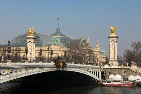 View on the Pont Alexandre III in Paris, a famous bridge over the Seine River in Paris. In the rear is the Grand Palais, a building created for the universal exposition of 1900.