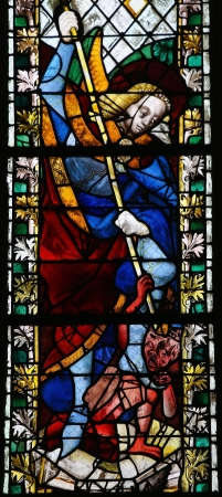 Saint Michael trampling Satan on a stained glass in the cathedral of Rouen, France, on February 10, 2013. This window was created more than 500 years ago, no property release is required.