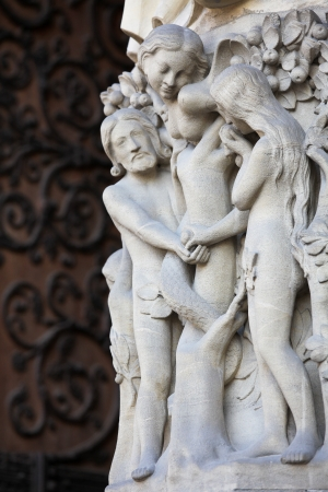 Adam and Eve eat the Forbidden Fruit at the Tree of Life in Paradise, sculpted at the Notre Dame Cathedral in Paris, France photo