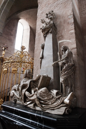mortality: Statue of a bishop and a personification of Death in the cathedral of Trier, Germany  This statue was created in the 17th Century, no property release is required  Editorial