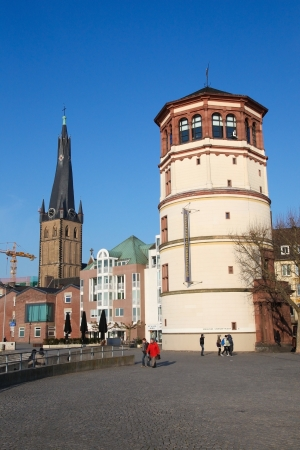 westfalen: Unidentified people in the center of Dusseldorf, Germany, with the tower of the 14th Century St Lambertus church and the Schlossturm tower on February 11, 2012.