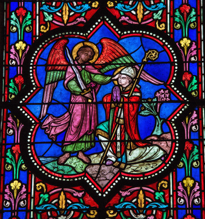 BAYEUX, FRANCE - FEB 12: Stained glass window depicting Saint Michael the Archangel and a bishop, in Bayeux, Calvados, France on February 12, 2013. This window was created in the 19th Century. No property release is required.