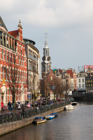 AMSTERDAM, THE NETHERLANDS - MARCH 25, 2011: View on the Singel canal and the famous Munt tower in Amsterdam, The Netherlands.