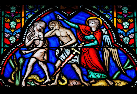 BRUSSELS, BELGIUM - JULY 26, 2012  Adam and Eve expelled from the Garden of Eden on a stained glass window in the cathedral of Brussels, Belgium  This window was created more than 100 years ago, no property release is required