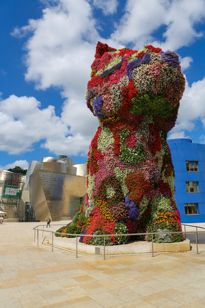 bilbo: BILBAO, SPAIN - JULY 10, 2014: Unidentified people near the work of art Puppy by Jeff Koons in front of the famous Guggenheim Museum in the center of Bilbao, Basque country, Spain.