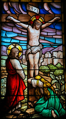 SAN ANDRES DE TEXEIDO, SPAIN - JULY 17, 2014: Stained glass window depicting the Crucifixion in the church of San Andres de Texeido, a famous Galician pilgrimage place in the Rias Altas region. This window was created more than 100 years ago, no property