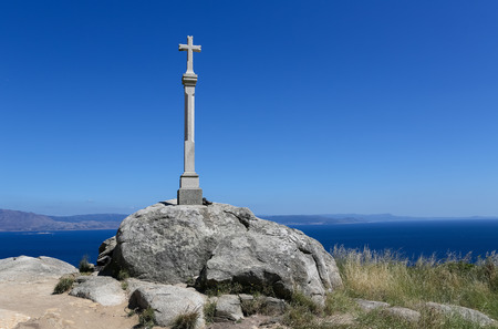 endpoint: Stone cross at the lighthouse of Cape Finisterre, the final destination for many pilgrims on the Way of St James to Compostela. It is located at the Costa da Morte in Galicia, Spain. In Roman times it was considered to be the end of the known world. Stock Photo