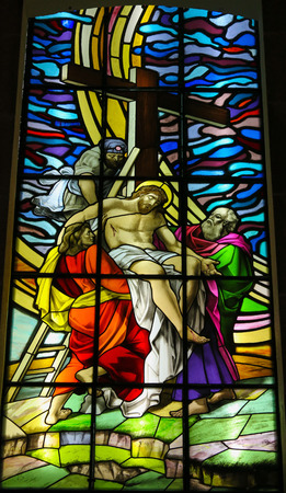 Stained glass window depicting Jesus taken from the cross in the Santos Passos church in Guimaraes, Portugal.