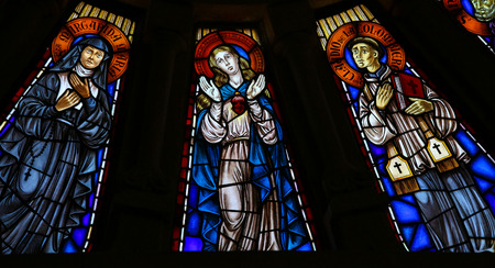 mother mary: VIANA DO CASTELO, PORTUGAL - AUGUST 4, 2014: Stained glass window depicting Mother Mary and two saints in the church of Viana do Castelo, Portugal.