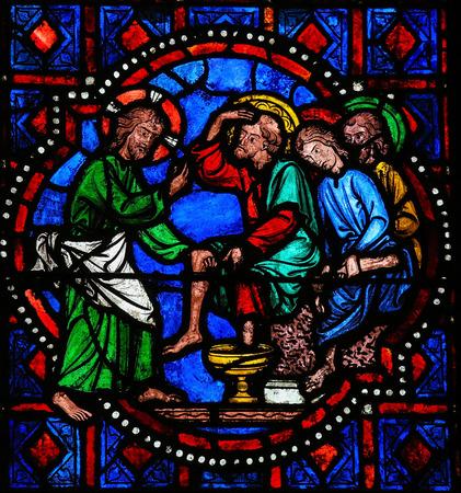 Glas in lood raam beeltenis van Jezus wast de voeten van Saint Peter bij het Laatste Avondmaal op Witte Donderdag in de kathedraal van Tours, Frankrijk. Redactioneel