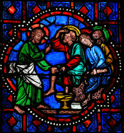 Stained glass window depicting Jesus washing the feet of Saint Peter at the Last Supper on Maundy Thursday in the Cathedral of Tours, France.