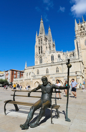 castille: BURGOS, SPAIN - AUGUST 13, 2014: Statue of Pilgrim on the Camino de Santiago in front of the gothic cathedral in Burgos, Castille, Spain.