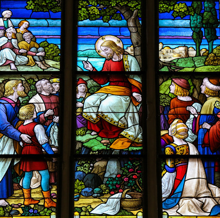 MECHELEN, BELGIUM - JANUARY 31, 2015: Stained Glass window depicting the miracle of Jesus feeding the multitude with loaves of bread and fish in the Cathedral of Saint Rumbold in Mechelen, Belgium. Sajtókép