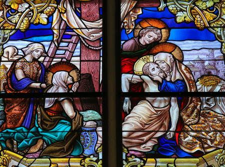mother of jesus: MECHELEN, BELGIUM - JANUARY 31, 2015: Stained Glass window, depicting Jesus taken from the Cross into Mother Marys arms on Good Friday, in the Cathedral of Saint Rumboldt in Mechelen, Belgium. Editorial