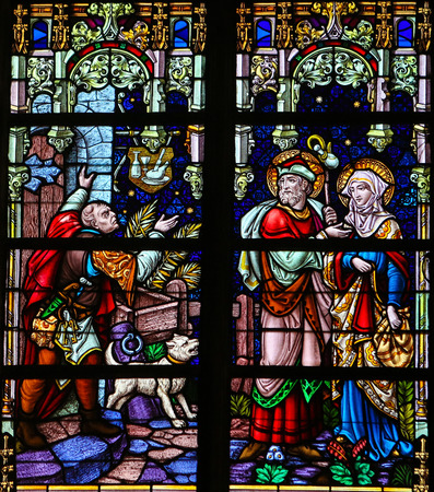 Mother Mary: MECHELEN, BELGIUM - JANUARY 31, 2015: Stained Glass window depicting Joseph and Mother Mary refused refuge in a tavern in Bethlehem, in the Cathedral of Saint Rumbold in Mechelen, Belgium.