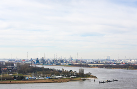 steam output: View on an oil refinery by the River Scheldt in the port of Antwerp, Belgium. Antwerp is the second largest port of Europe and a major petrochemical center.