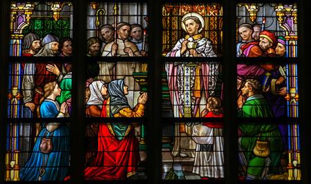 'S HERTOGENBOSCH, NEDERLAND - 23 juli 2011: Stained Glass Window beeltenis van een heilige uitvoeren van het sacrament van de Heilige Communie in Den Bosch Kathedraal, Noord-Brabant. Redactioneel