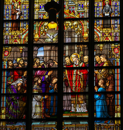 sainthood: S HERTOGENBOSCH, THE NETHERLANDS - JULY 23, 2011: Stained Glass Window depicting Saint Lambertus anointing the Taxandrians during the Confirmation, the rite of initiation in the Catholic church. This window is located in Den Bosch Cathedral, North Braban Editorial