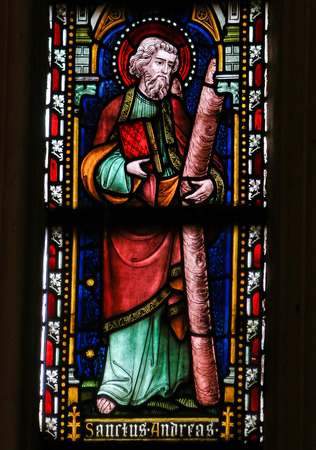 ST TRUIDEN, BELGIUM - APRIL 21, 2013: Stained glass window, depicting Saint Andrew or Andreas and his cross, in the Cathedral of Saint Truiden in Limburg, Belgium.