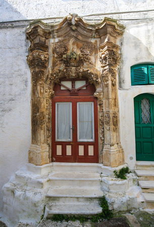 south italy: Entrance door with baroque decoration in the medieval town Ostuni in Puglia, South Italy. Stock Photo