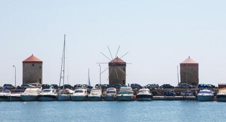 rhodes: RHODES, GREECE - JUNE 12, 2015: Windmills at the Harbour of Rhodes, Greece