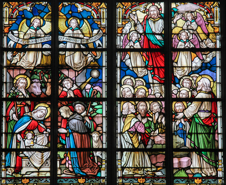 STABROEK, BELGIUM - JUNE 27, 2015: Stained glass window depicting a Nativity Scene at Christmas and the Resurrected Christ in the Church of Stabroek, Belgium. Sajtókép