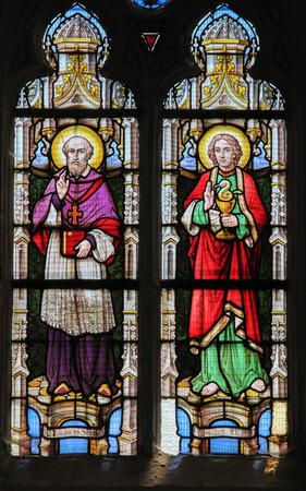 evangelist: STABROEK, BELGIUM - JUNE 27, 2015: Stained glass window depicting Saint Franciscus and Saint John the Evangelist in the Church of Stabroek, Belgium.