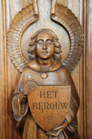 sinful: HAACHT, BELGIUM - MAY 30, 2015: Statue of an angel  holding a sign with the word Repentance at a Confessional in the Church of Haacht, Belgium. Editorial
