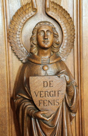 clemency: HAACHT, BELGIUM - MAY 30, 2015: Statue of an angel  holding a sign with the word Forgiveness in Dutch at a Confessional in the Church of Haacht, Belgium. Editorial