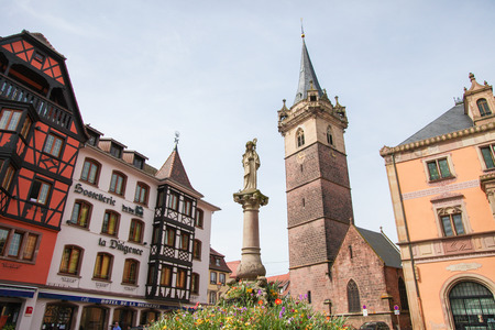 des vins: OBERNAI, FRANCE - MAY 11, 2015: Chapel tower, Sainte Odile fountain and town hall on the market square of Obernai, Bas-Rhin, Alsace, France Editorial