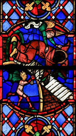 dualistic: Stained glass window depicting a Devil and an Angel fighting for the soul of a monk in the Cathedral of Tours, France.