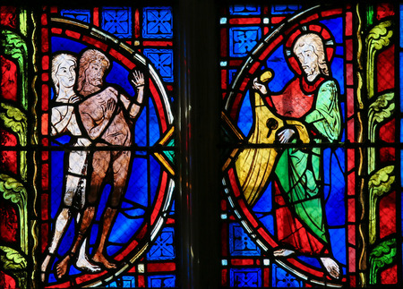expel: Stained glass window depicting Adam and Eve in the Cathedral of Tours, France.