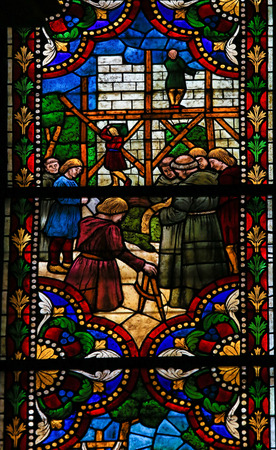 castile and leon: LEON, SPAIN - AUGUST 12, 2014: Stained Glass window depicting the Construction of a Gothic Cathedral in the Cathedral of Leon in Castile and Leon, Spain.
