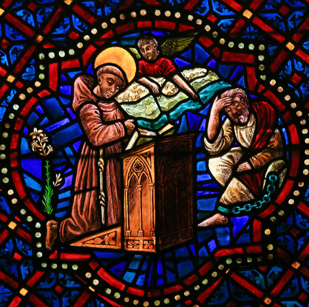catholic stained glass: LEON, SPAIN - AUGUST 12, 2014: Stained Glass window depicting a Catholic Saint praying to Christ in the Cathedral of Leon in Castile and Leon, Spain. Editorial