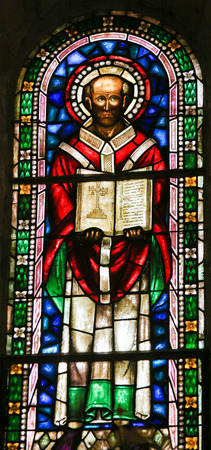 catholic stained glass: LEON, SPAIN - JULY 17, 2014: Stained glass window depicting a Catholic Saint and the Bible in the Basilica of San Isidoro in Leon, Castille and Leon, Spain.