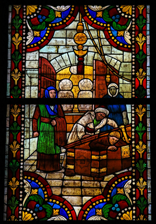 catholic stained glass: LEON, SPAIN - JULY 17, 2014: Stained glass window depicting a Catholic Saint hiding in a coffin in the cathedral of Leon, Castille and Leon, Spain.