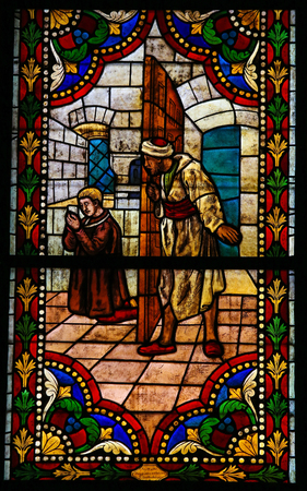 LEON, SPAIN - JULY 17, 2014: Stained glass window depicting a praying Catholic Saint held captive by Moors, in the cathedral of Leon, Castille and Leon, Spain. Redakční