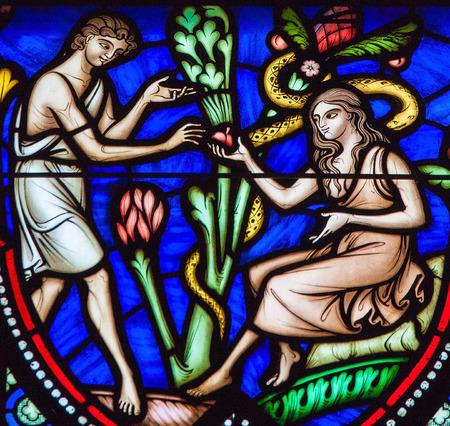 Bruselas, Bélgica - 26 de julio de 2012: Adán y Eva comer del fruto prohibido en el Jardín del Edén en un vitral en la catedral de Bruselas. Editorial