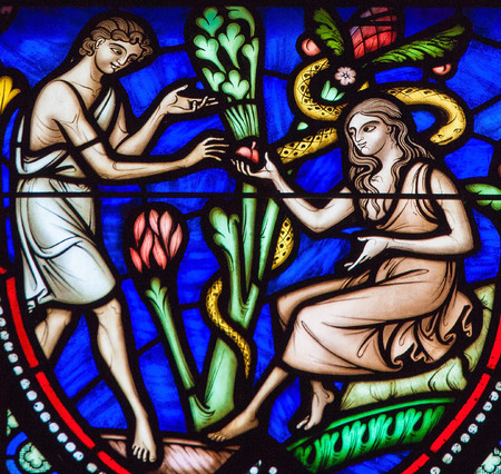BRUSSELS, BELGIUM - JULY 26, 2012: Adam and Eve eating the Forbidden Fruit in the Garden of Eden on a stained glass window in the cathedral of Brussels. Imagens - 54680925