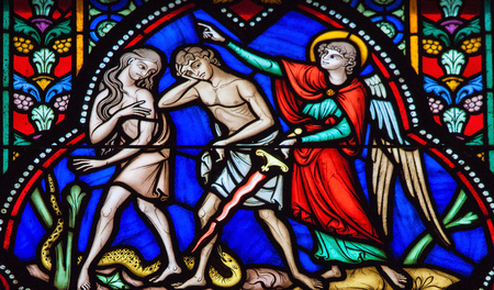 BRUSSELS, BELGIUM - JULY 26, 2012: Adam and Eve expelled from the Garden of Eden on a stained glass window in the cathedral of Brussels, Belgium.