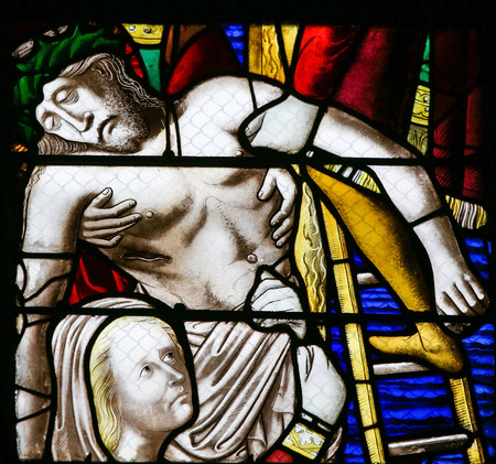 are taken: ROUEN, FRANCE - FEBRUARY 10, 2013: Jesus taken from the cross on a stained glass in the cathedral of Rouen, France