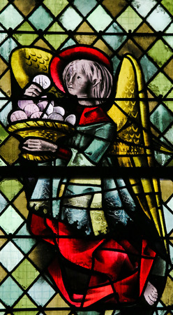 ROUEN, FRANCE - FEBRUARY 10, 2013: Angel with a Eucharist on a stained glass in the cathedral of Rouen, France