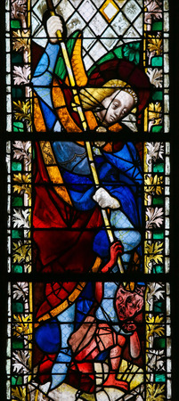 ROUEN, FRANCE - FEBRUARY 10, 2013: Saint Michael trampling Satan on a stained glass in the cathedral of Rouen, France