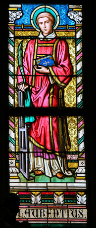 laurence: PRAGUE, CZECH REPUBLIC - APRIL 2, 2016: Stained Glass window in St. Vitus Cathedral, Prague, depicting Saint Lawrence of Rome, an early Christian martyr.