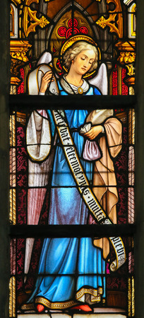 lier: LIER, BELGIUM - MAY 16, 2015: Stained Glass window in St Gummarus Church in Lier, Belgium, depicting and Angel holding a money purse, symbol for charity.