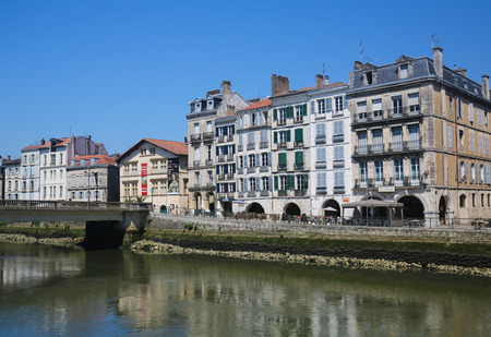 gascony: BAYONNE, FRANCE - JULY , 2016: Old houses by the river La Nive in the center of Bayonne, a city in the Aquitaine region of south-western France. Editorial