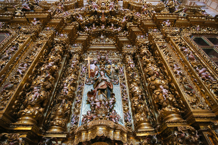 altarpiece: Huge, magnificent gilt wood altarpiece in the national Portuguese artarpiece style, in the New Cathedral or Se Nova of Coimbra in Portugal Editorial