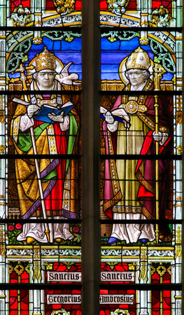 theologian: Stained Glass window depicting Saints Gregory and Ambrose, in the Cathedral of Mechelen, Belgium.